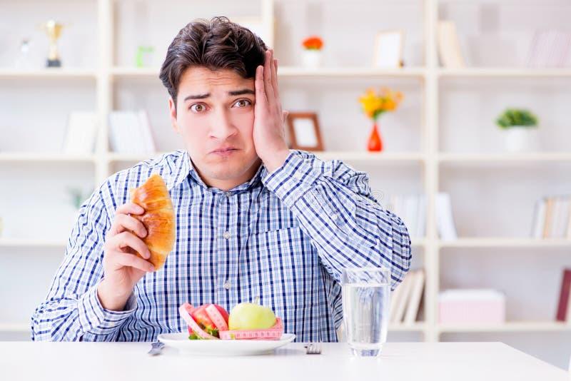 Mannen som har dilemma mellan sund mat och bröd, i att banta, lurar fotografering för bildbyråer