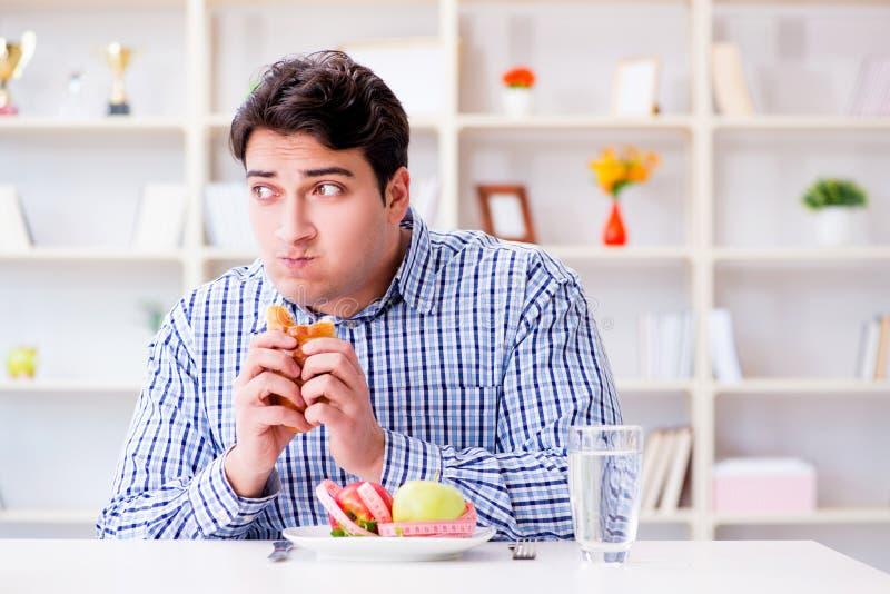 Mannen som har dilemma mellan sund mat och bröd, i att banta, lurar arkivfoto