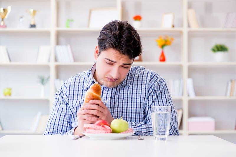 Mannen som har dilemma mellan sund mat och bröd, i att banta, lurar royaltyfri bild