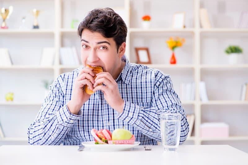 Mannen som har dilemma mellan sund mat och bröd, i att banta, lurar royaltyfria bilder