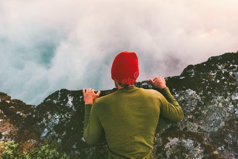 Mannen som ner ligger på de ovannämnda molnen för kantklippan, stirrar in i avgrund arkivfoto