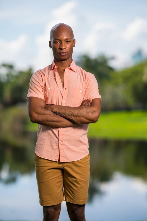 Mannen som poserar i rosa knappskjorta med armar, korsade Manlig modell för afrikansk amerikan med uttryckslöst uttryck och oskar fotografering för bildbyråer