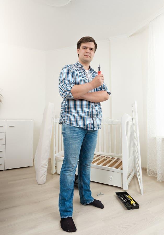 Mannen som poserar med hjälpmedel på demontert, behandla som ett barn säng på sovrummet arkivfoto