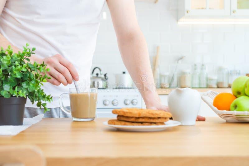 Mannen som r?r kaffe med, mj?lkar i genomskinlig kopp p? k?ksbordet Morgonkaffe eller framst?llning av frukostbegrepp arkivfoto