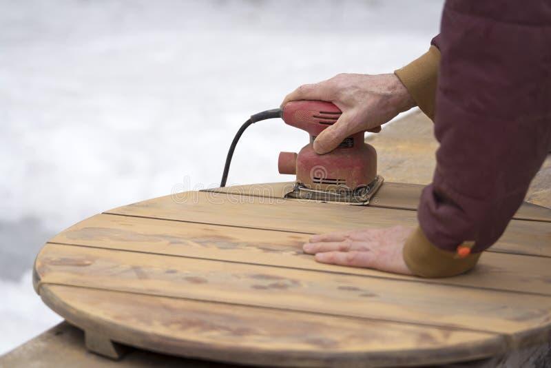 Mannen som Refinishing en utomhus- cederträtabell med, gömma i handflatan slipmaskinen arkivfoton