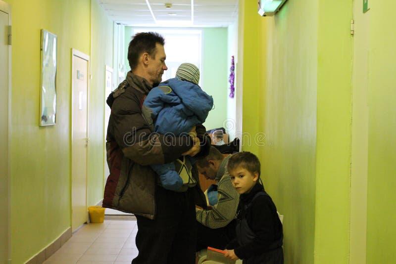 Mannen som rymmer ett barn, och barn står i linje på sjukhuset mottar fördelar i en väntande på erkännande för offentlig institut royaltyfri fotografi