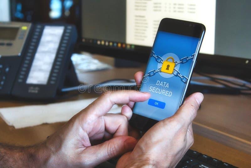Mannen som rymmer ett mobilt, ilar telefonen med en applikation för datasäkerhet som visar en gul hänglås arkivbilder