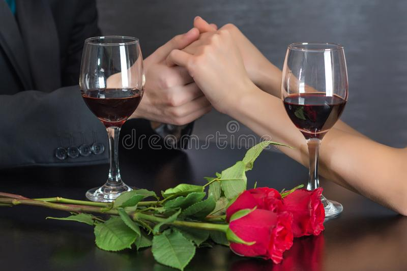 Mannen som rymmer händer av flickan på restaurangtabellen med två rött vinexponeringsglas, och röda rosor blommar royaltyfria foton