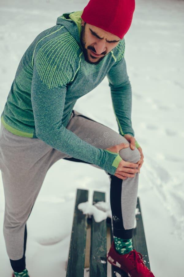 Mannen som rymmer hans knä i, smärtar på en snöig dag royaltyfria bilder