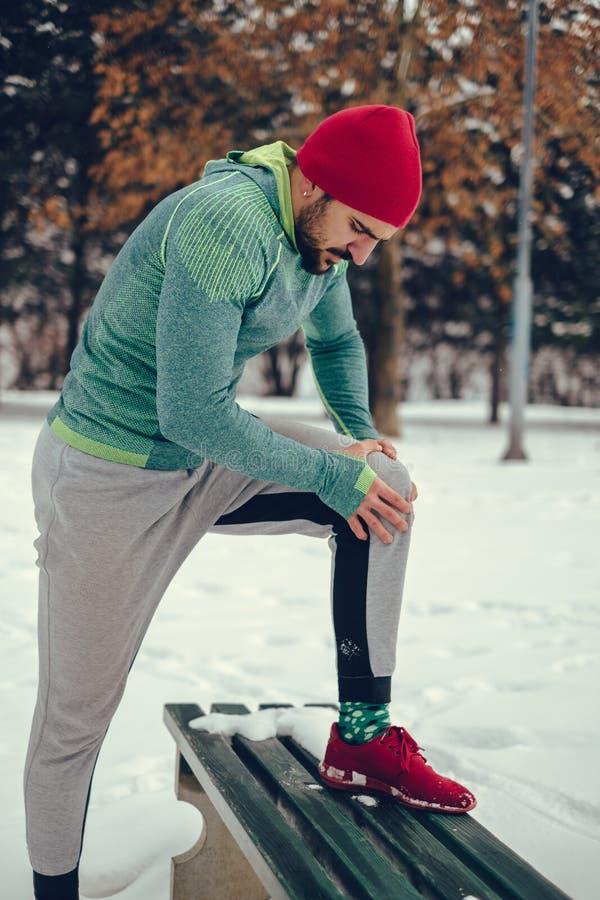Mannen som rymmer hans knä smärtar in, på en vinterdag royaltyfria foton