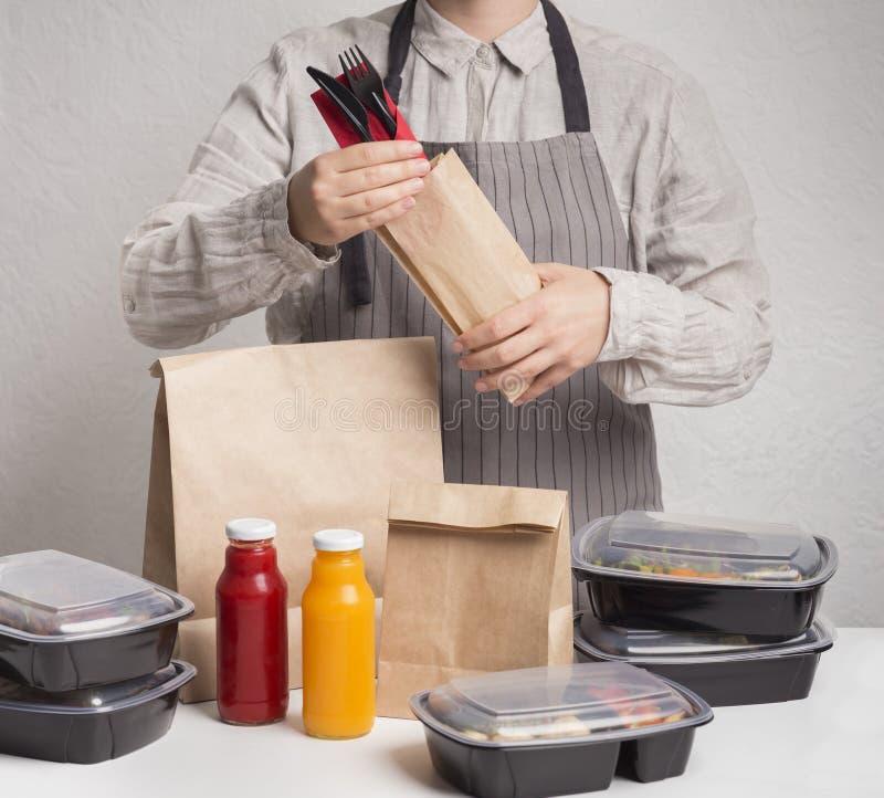 Mannen som samlar beställning av dayily heathy, ransonerar av mat i askar royaltyfria bilder
