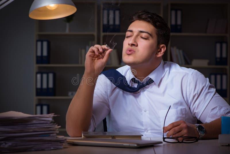 Mannen som sent blir på natten och röker marijuana fotografering för bildbyråer