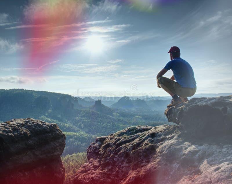 Mannen som sitter på, vaggar klippan i berg och att hålla ögonen på på soluppgånglandskap paradis för natur för sammansättningsde royaltyfri foto