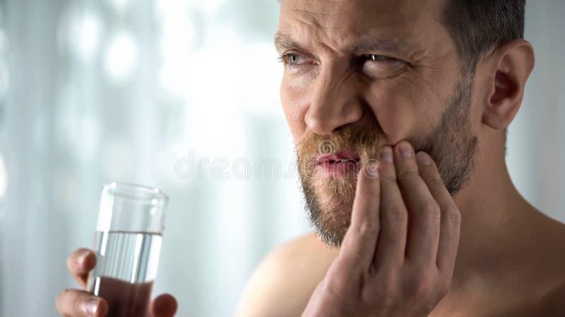 Mannen som sköljer tanden med vatten, hypersensitivity, skarpt tand-, smärtar, gingivit royaltyfri bild