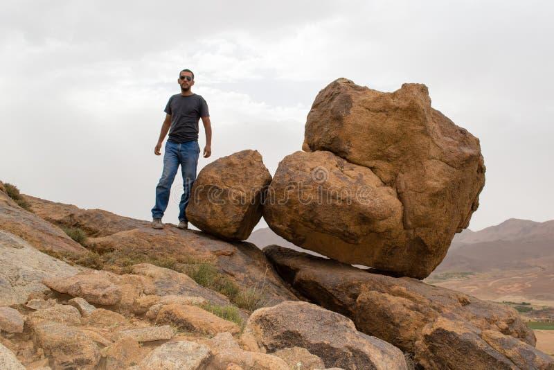 Mannen som står near den stora rullningsrundan, vaggar på kanten av ett berg royaltyfri fotografi