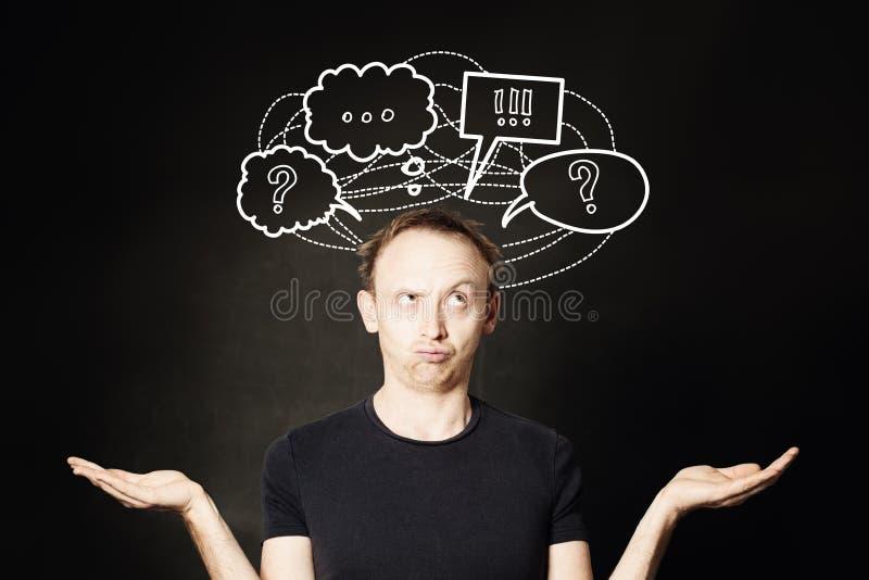 Mannen som tänker med frågefläcken, och handteckningen skissar bubblan på svart tavlabakgrund Val, problem och lösningsbegrepp royaltyfria bilder