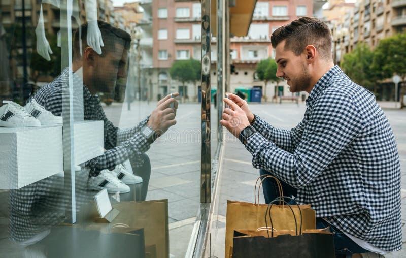 Mannen som tar ett foto av, shoppar fönstret av ett modelager arkivfoton