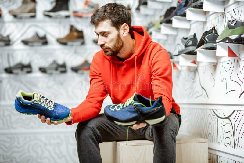 Mannen som väljer fotvandra skor i, shoppar royaltyfri bild