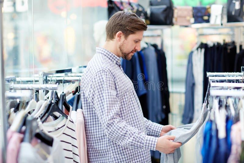 Mannen som väljer kläder shoppar in arkivfoton