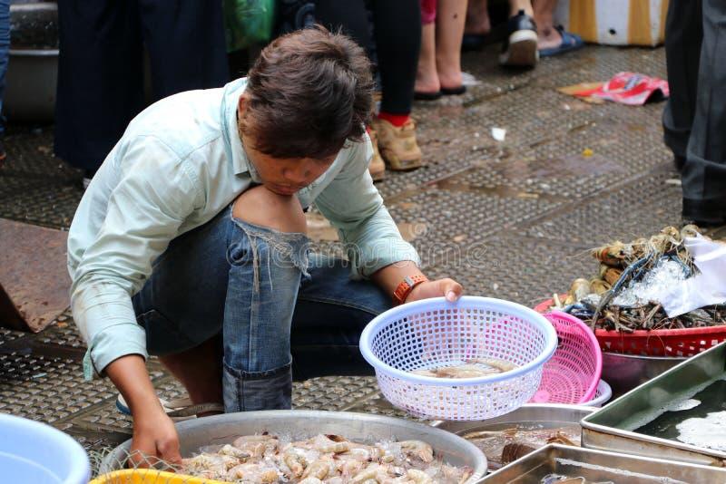 Mannen som väljer räka till korgen på den nya marknaden i den centrala marknaden, en stor marknad med otaligt, stannar av gods royaltyfri bild