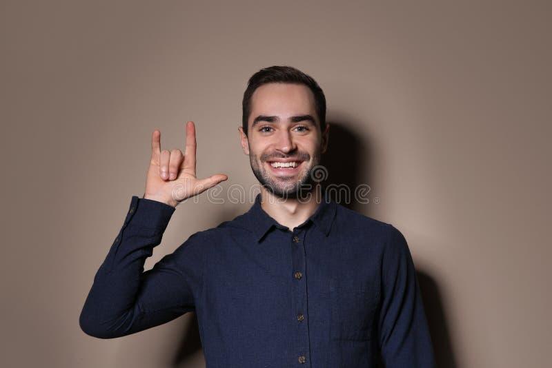 Mannen som visar ÄLSKAR JAG, DIG gesten i teckenspråk royaltyfria bilder