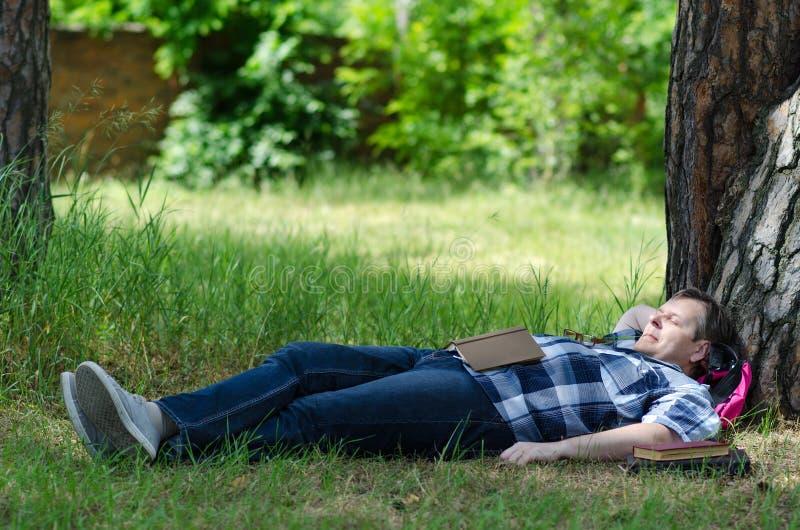 Mannen sover med den öppna boken på gräsmatta på gammalt sörjer arkivbild