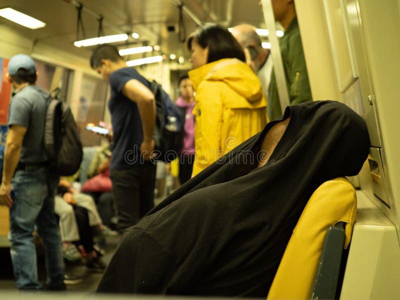 Mannen sover med skjortan över hans huvud på en fullsatt BARTgångtunnelbil royaltyfria foton