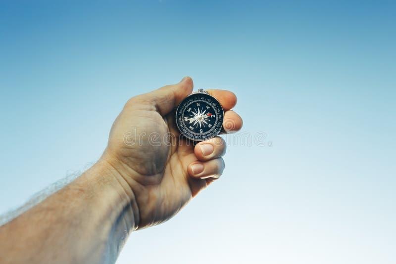 Mannen spanar den utforskareSearching Direction With kompasset på blå himmel royaltyfri fotografi