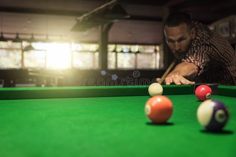 Mannen spelar billiard eller snooker royaltyfria foton