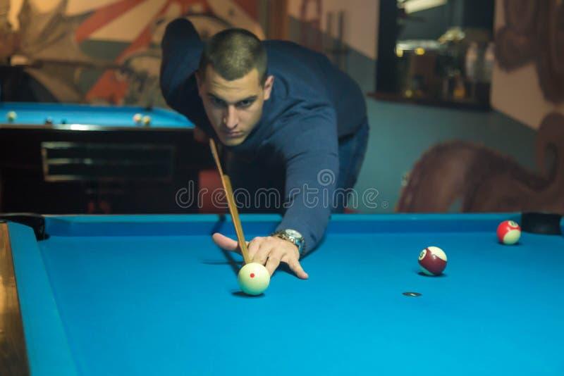 Mannen spelar en billiard på klubban arkivfoton