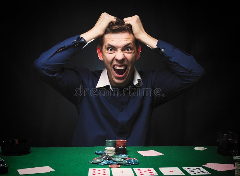 Mannen spelar poker Emotionell kuggning i leken, lek över för kort royaltyfria bilder