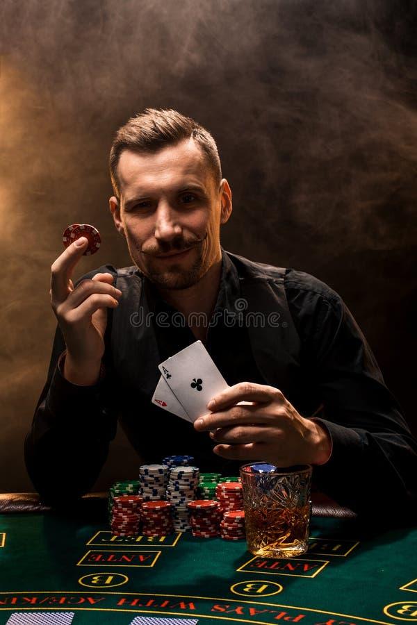 Mannen spelar poker med en cigarr och en whisky, kort för en manshow två i handen som segrar alla chiper på tabellen royaltyfria bilder