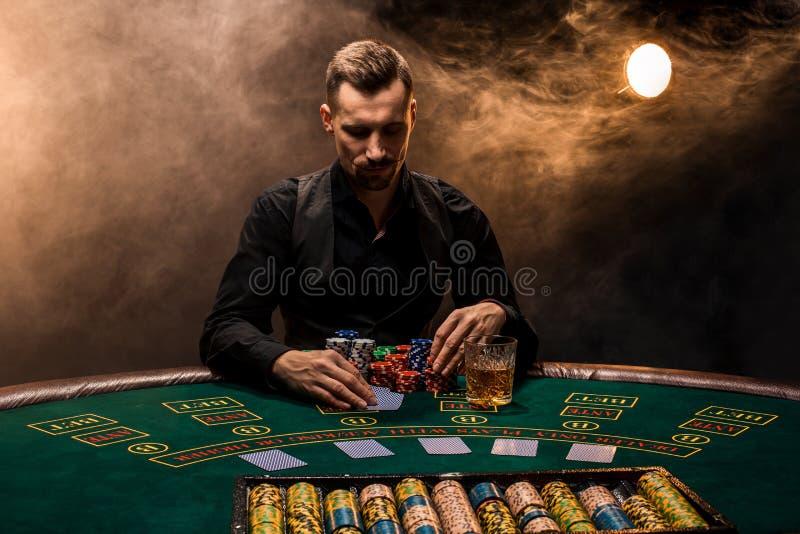 Mannen spelar poker med en cigarr och en whisky En man som segrar alla chiper på tabellen med tjock cigarettrök fotografering för bildbyråer