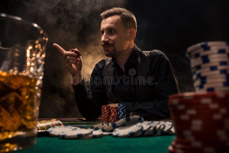 Mannen spelar poker med en cigarr och en whisky En man som segrar alla chiper på tabellen med tjock cigarettrök royaltyfri foto
