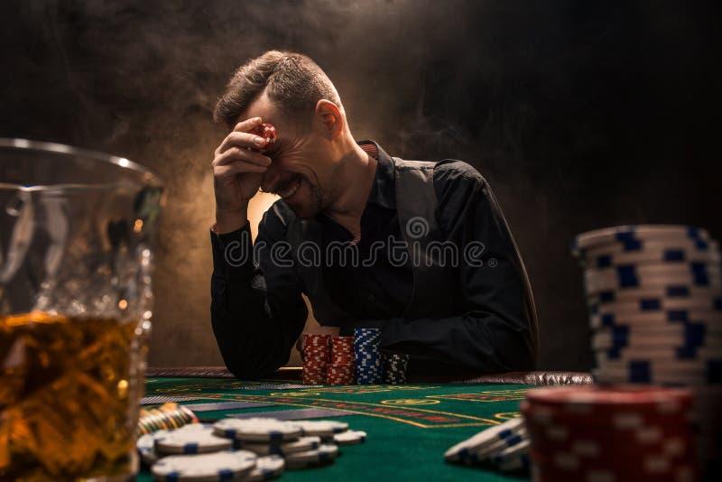 Mannen spelar poker med en cigarr och en whisky En man som segrar alla chiper på tabellen med tjock cigarettrök royaltyfria bilder
