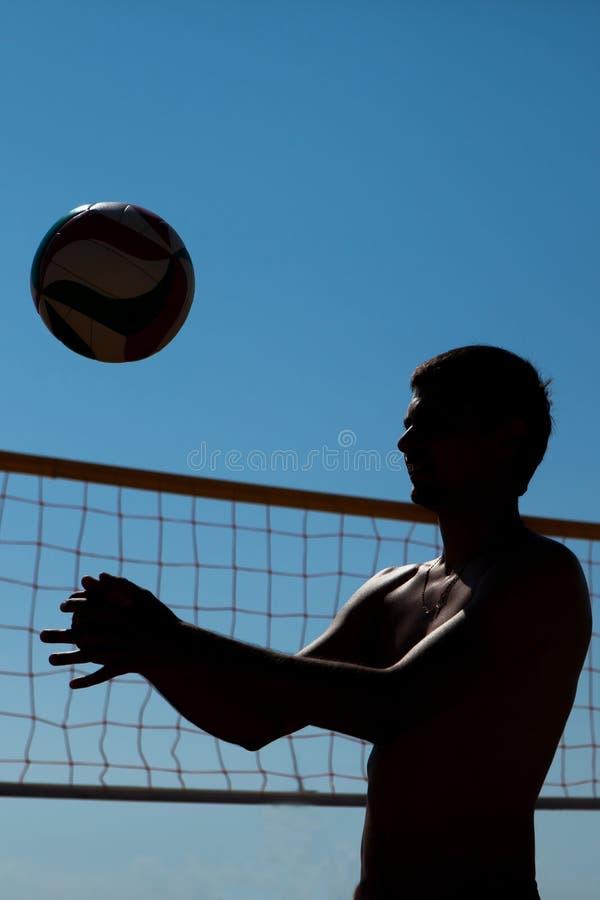 Mannen spelar volleyboll arkivfoto