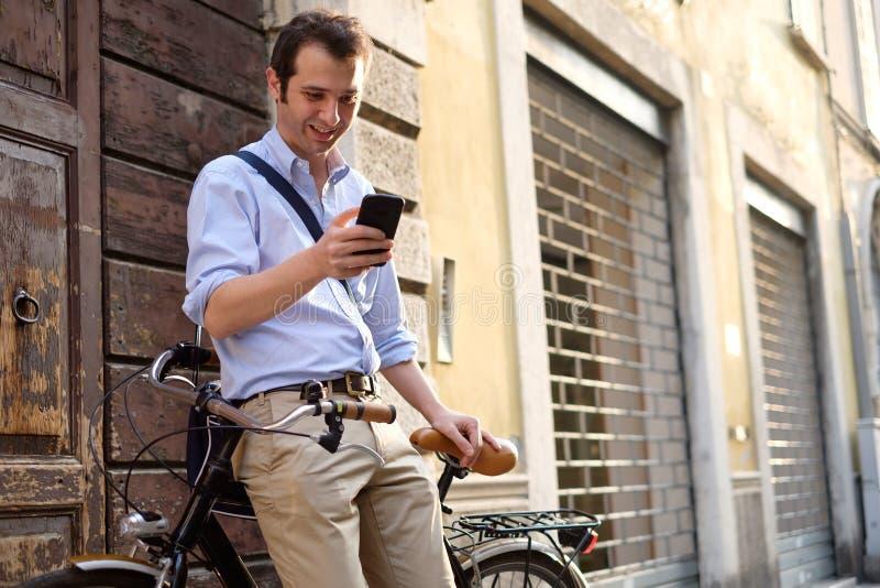 Mannen står bredvid hans cykel royaltyfri fotografi