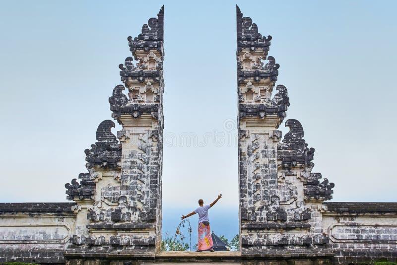 Mannen står i porten av den Lempuyang templet på Bali isalnd, royaltyfri fotografi