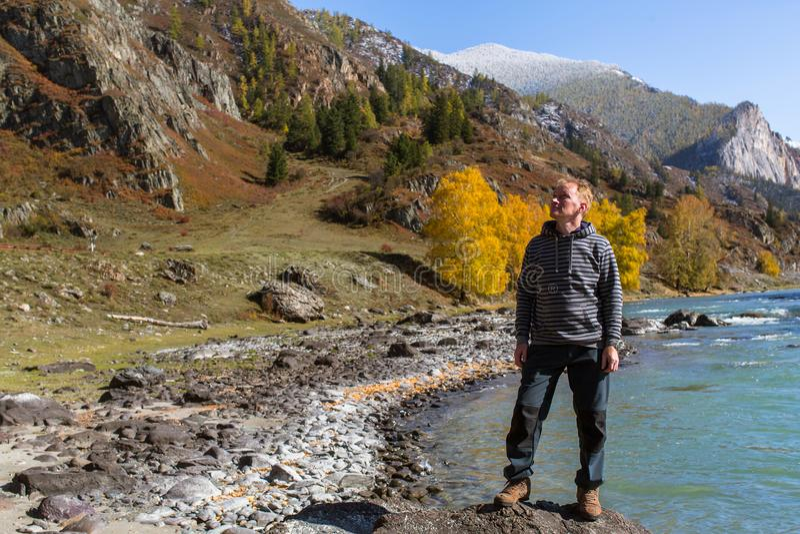 Mannen står på banken av den Katun floden i de Altai bergen arkivbild