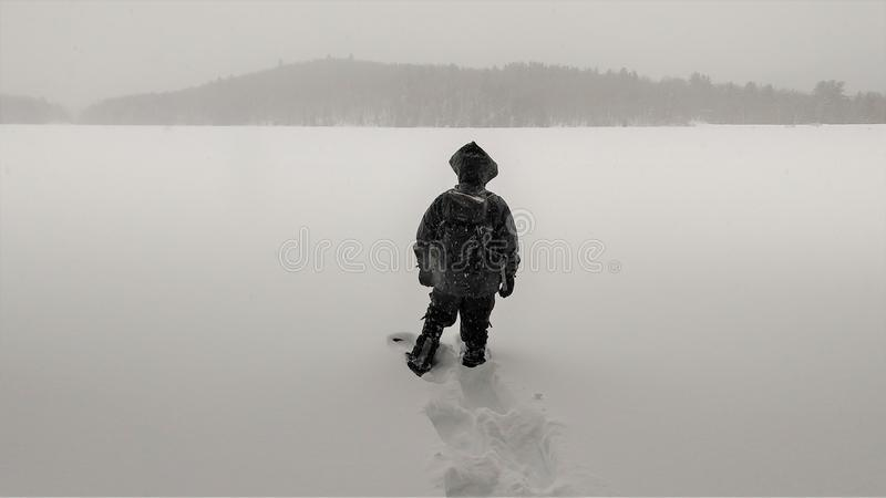 Mannen står på den djupfrysta sjön i snöstorm arkivbild