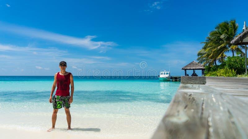 Mannen står på stranden Lyxig ö i Maldiverna, träbrygga in i det blåa tropiska havet arkivfoto