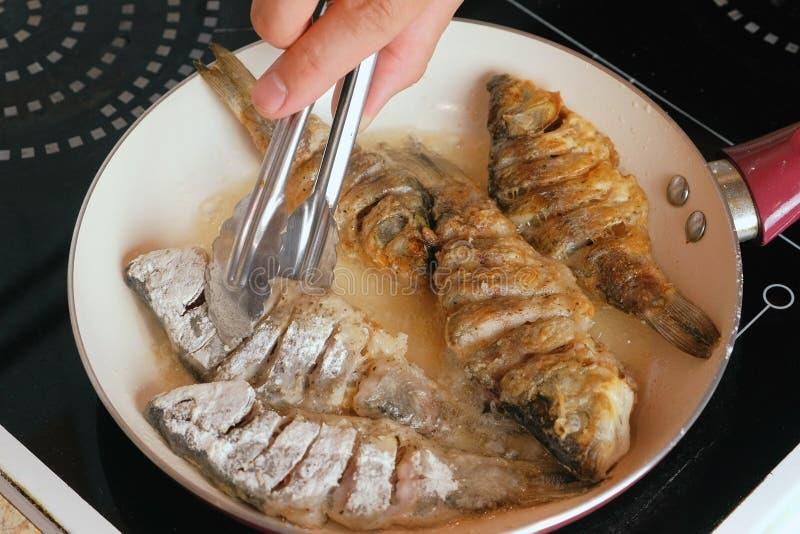 Mannen stekte fisken i olja i en panna Närbildman` s räcker flipsfisken med kulinarisk tång royaltyfri fotografi