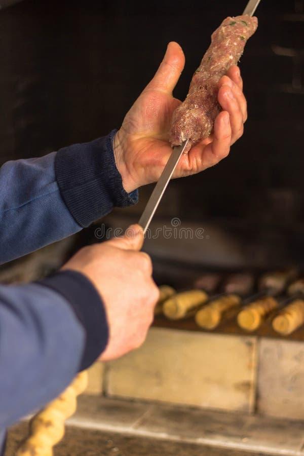 Mannen stränger kött på en steknål royaltyfria foton