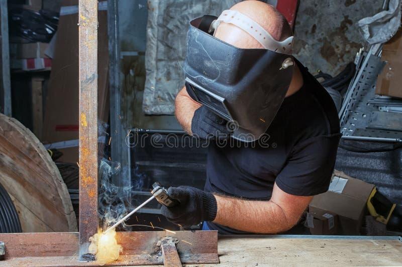 Mannen svetsar en metallbågsvetsningmaskin arkivfoto