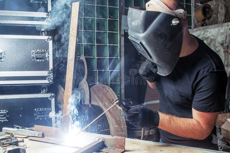 Mannen svetsar en metallbågsvetsningmaskin royaltyfri fotografi