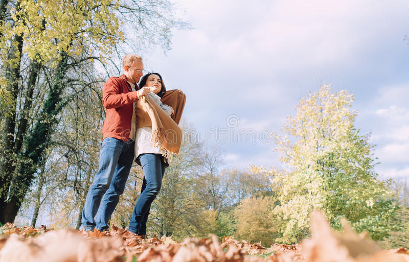 Mannen täcker hans fru som skuldror med den varma sjalen i höst parkerar royaltyfria foton