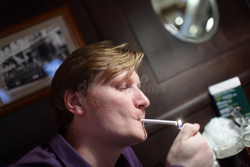 Mannen tänder en cigarett royaltyfria bilder