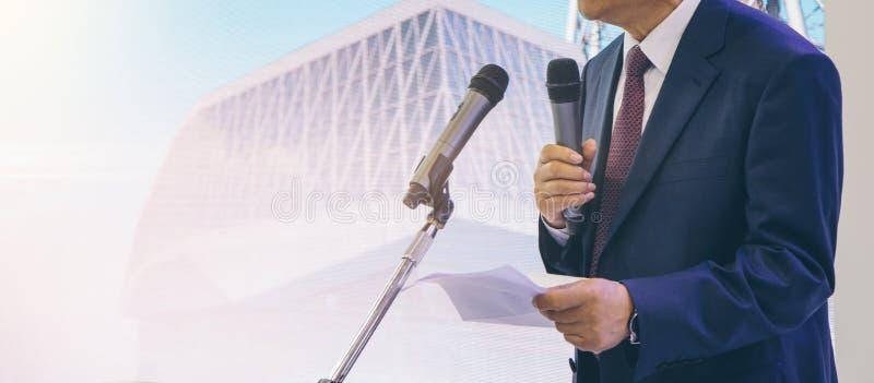 Mannen talar in i mikrofonen på ett affärsmöte royaltyfri fotografi