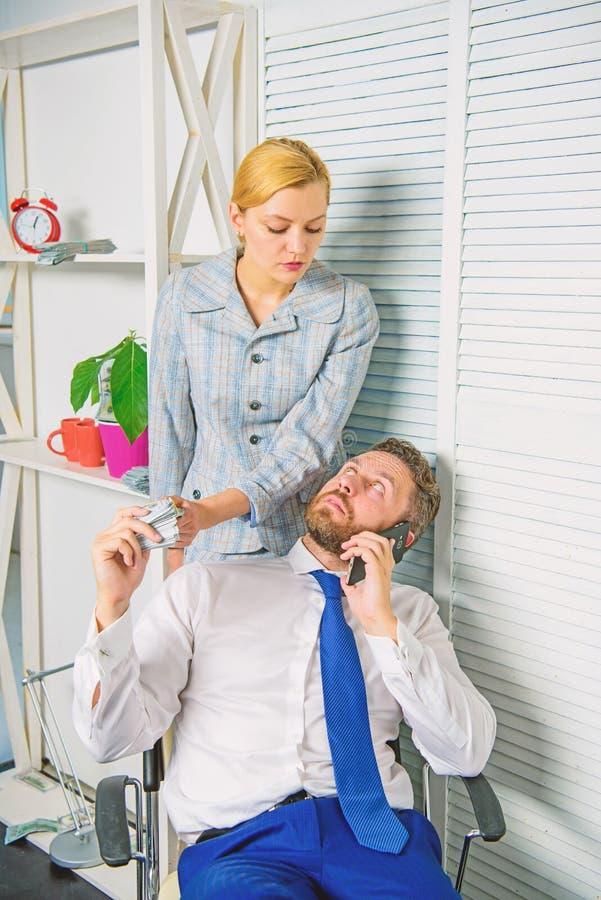 Mannen talar mobiltelefonen f?r att fr?ga f?r pengar Finansiellt bedr?geribrott f?r medbrottslingar Mannen och kvinnan tj?nar pen royaltyfri foto