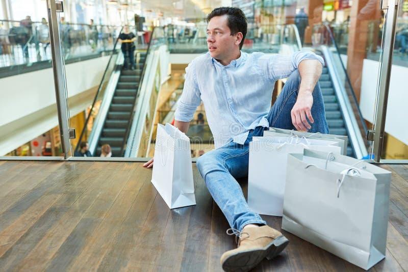 Mannen tar ett avbrott, medan shoppa royaltyfri foto